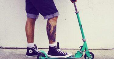 Mann mit Fuß auf Tretroller