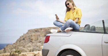 Frau sitzt auf Auto mit Strand im Hintergrund