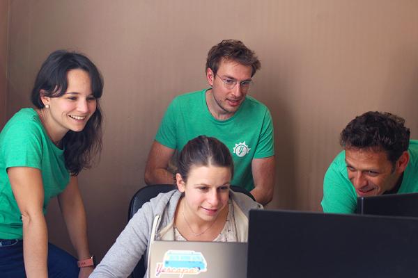 Mitarbeiter sitzen am Laptop im Büro von Yescapa