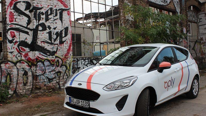 Oply Carsharing Auto vor Mauer mit Graffiti in Berlin
