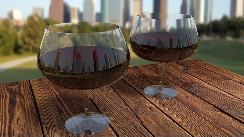 Rotweingläser mit Großstadt im Hintergrund