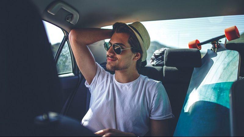Junger Mann sitzt mit Skateboard in einem Auto mit Cabify-Service