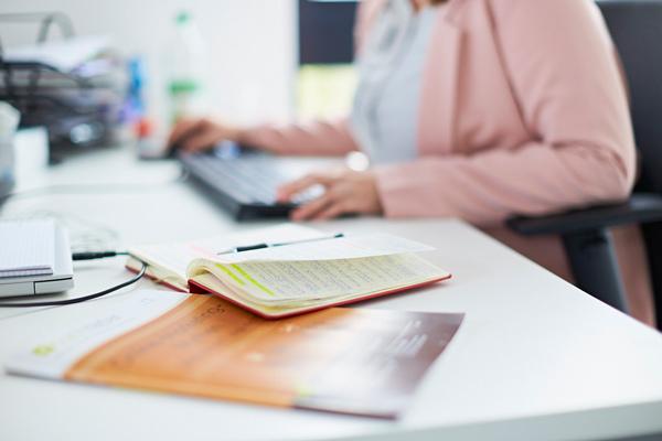 Blick auf den Schreibtisch mit Tastatur und Notizbuch.