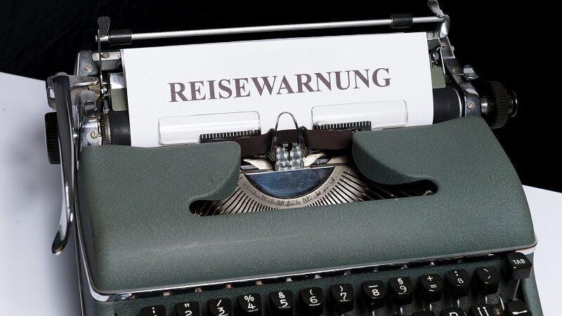Reisewarnung, Schreibmaschine, Corona, Urlaub